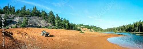 Fényképezés Quad ATV stands on sandy terrain at a beautiful lake.