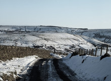 View Of Yorkshire Moors Covered In Snow With A Country Road Going Downhill And The Pennines On The Horizon With Paths And Fields On A Bright Sunny Day