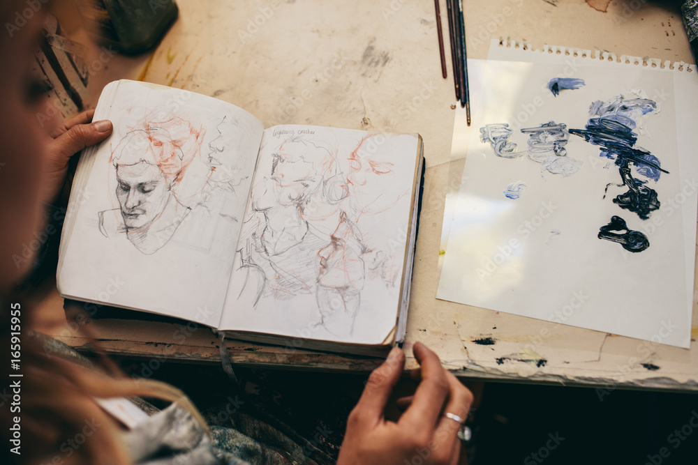Fototapety, obrazy: Female artist looking at sketches in her studio