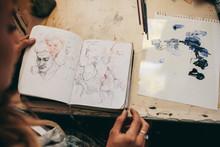 Female Artist Looking At Sketc...