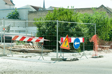 Street Road Construction Reparation Site With Safety Fence, Barrier And Work Ahead Sign.