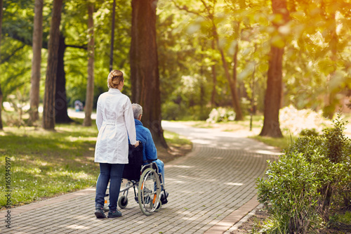 nurse helping elderly man on wheelchair outdoor. Fotobehang
