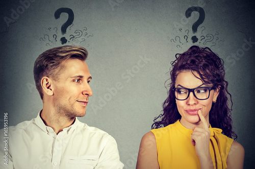 Man and woman with question mark looking at each other with interest Wallpaper Mural