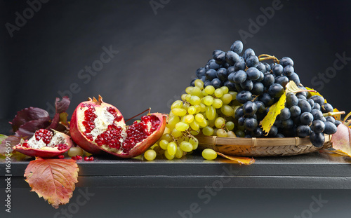 Foto  Blue and white grapes with pomegranate