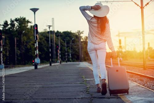 Plakat Młoda uśmiechnięta kobieta z bagażowym odprowadzeniem w świetle słonecznym. Tło podróży. Ciepłe odcienie.