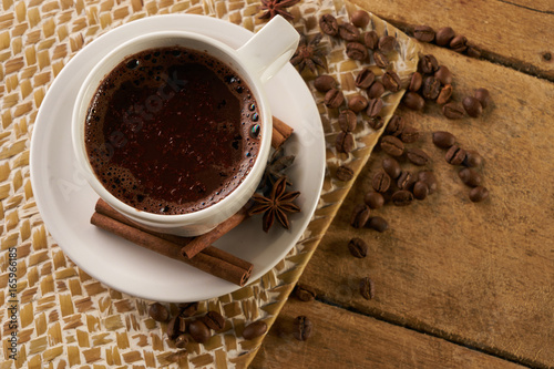 In de dag Chocolade Cup of coffee with cinnamon sticks anise and arabica coffee beans on old wooden rustic background with copy space.