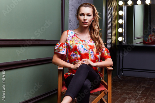 Fotografía  Sexy woman wear fashion clothes color blouse black pants seat on chair director actress actor film maker dressing room mirror lamp light model pose glamor makeup interior studio blond hair beautiful