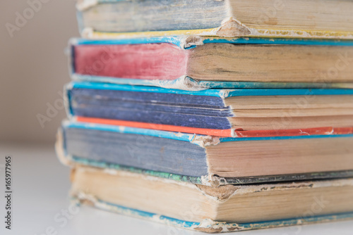 Valokuva  Vintage hardcover books in pile on white table with neutral background