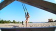Beautiful, athletic, sexy young woman in swimsuit, coach, instructor, performs, doing exercises with fitness trx system, TRX suspension straps. On the beach, in summer, in sun rays.