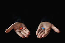 Red And Blue Pills On Hand Isolated
