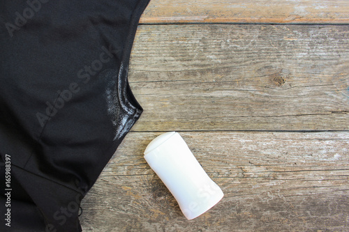 Photo White spot on the dress armpit and deodorant on a wooden background