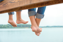 Two Brothers  Swung Their Legs From The Wooden Pier  .Family Vacation On The Lake.