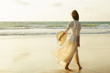 Woman Wearing Beautiful White Dress Is Walking On The Beach During Sunset