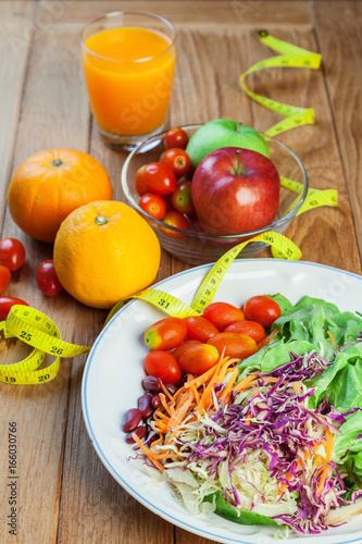Healthy concept with mixed fruits and vegetables on wooden background
