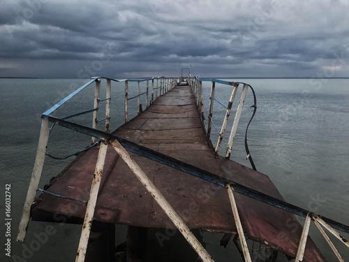Poster  старый ржавый мост стоит в море после урагана