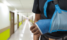 Man's Arm In Cast And Sling With Blurred Hospital Background