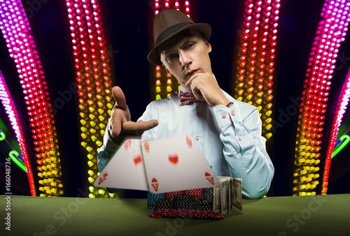 Beautiful young man on a beautiful background playing poker Poster
