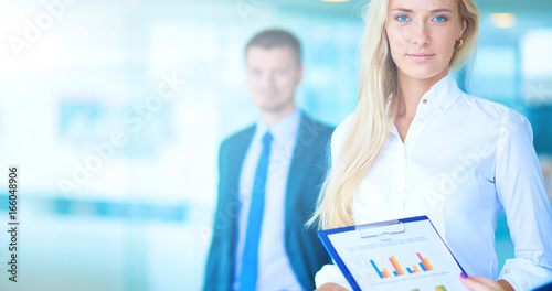 Fotografia  Portrait of young businesswoman in office with colleagues in the background