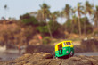 Auto rickshaw driving past palm tree forest in India. Public transport model in natural landscape of Asia