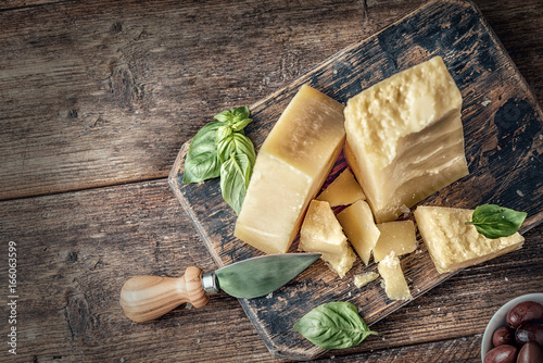 Fotografie, Obraz  Parmesan cheese on wooden board with basil leaves