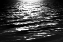 Rippled Water Surface At Night. Light On The Water From A Lighthouse Or Rescue Boat (lifeboat). Spotlight On The Water. Background