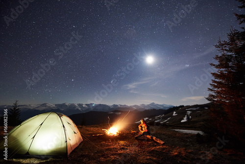 Male Tourist Have A Rest In His Camp Near The Forest At Night Man Sitting Campfire And Tent Under Beautiful Sky Full Of Stars Moon