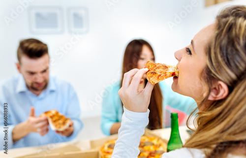 Foto op Canvas Kruidenierswinkel Workers eating pizza in the office