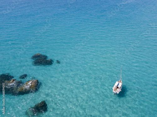 Vista aerea di una barca ormeggiata che galleggia su un mare trasparente Canvas Print
