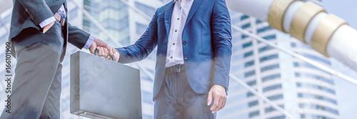 Fotografia Businessman transfer deal, business black briefcase exchange urban city background