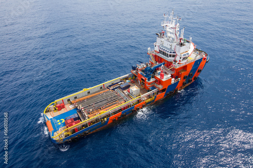 Crew boat and supply vessel at offshore oil and gas platform while loading piping, tubing for drilling operation of oil and gas reservoir.