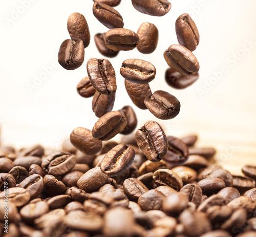 Fototapeta premium Zbliżenie spadające lub latające kawowe fasole na białym tle
