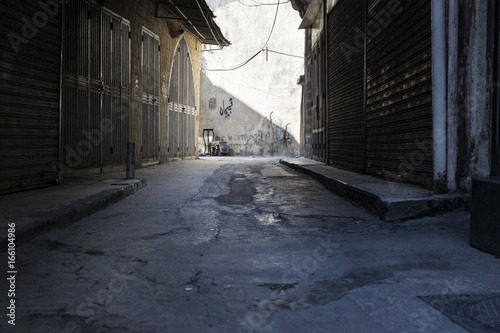 Dark shopstreet at Fridayafternoon with sunlight at the end of the street in the souks of Tripoli, Lebanon