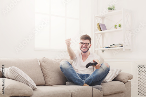 Happy young man at home playing video games and wins