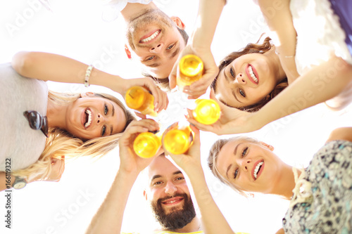 Group of young people cheering and having fun outdoors with drinks Poster