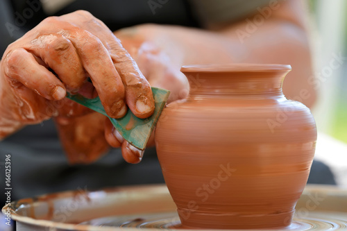 Fotografija Potter making ceramic pot on the pottery wheel