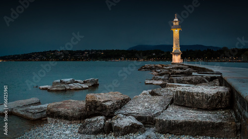 A wide angle shot of a lit lighthouse in Lake Geneva, Switzerland during early e Canvas Print