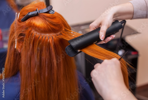 Hairdresser makes hairstyle girl with long red hair in a beauty salon. Straightening hair ironing. Professional hair care.