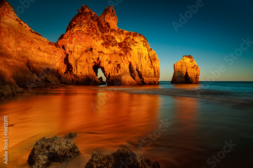 A long exposure, golden hour sunset picture of the Alvor beach in Algarve, Portugal
