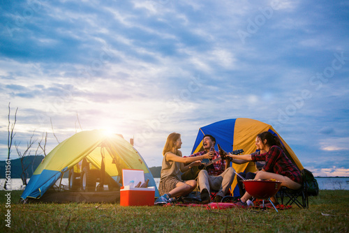 Canvas Prints Camping Group of man and woman enjoy camping picnic and barbecue at lake with tents in background. Young mixed race Asian woman and man. Young people's hands toasting and cheering bottles of beer.