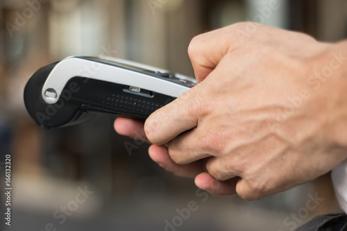 Close-up: Man`s hands are working with a debit card reader