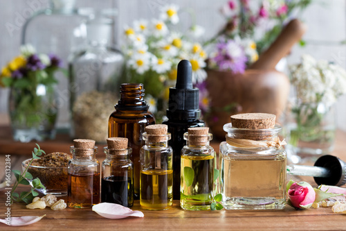 Fototapeta  Selection of essential oils with various herbs and flowers