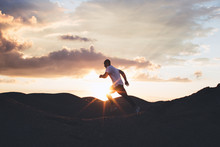 Male Athlete Trains In The Open Air. Running At Sunset Outdoors. Silhouette Of A Runner On Background Of Beautiful Sunset