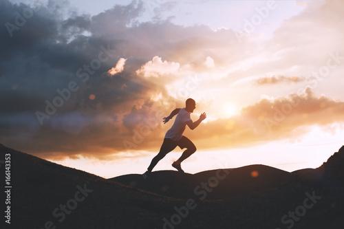 Athlete runs quickly through the hills outdoors at sunset Fototapeta
