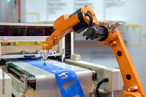Fotografiet  Robot gripping a workpiece out of the machine via a conveyor belt for smart factory, industry 4