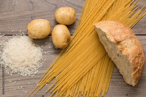 Fotomural Spaghetti, rice, potatoes, and bread, on a wooden table