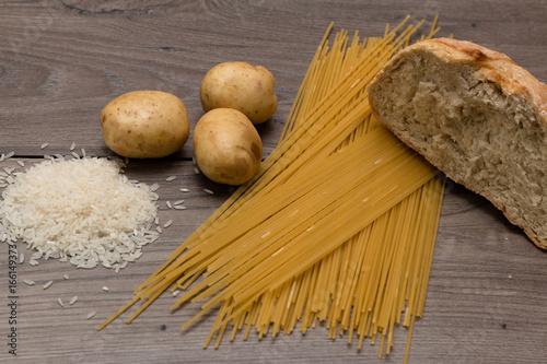 Fotografía  Spaghetti, rice, potatoes, and bread, on a wooden table