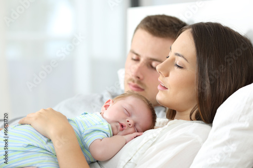 Foto  Tired parents sleeping with their baby