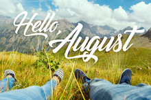 Hello August Text With Couple's Legs Together On View Of The Green Valley And High Mountains. Nature Calendar Background. Travel, Vacation, Holiday, Unity With Nature, Adventure Concept.