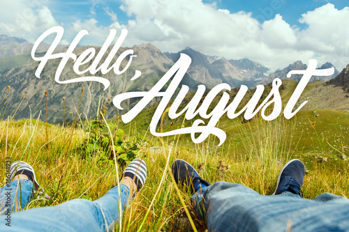Obraz Hello august text with couple's legs together on view of the green valley and high mountains. Nature calendar background. Travel, vacation, holiday, unity with nature, adventure concept. - fototapety do salonu