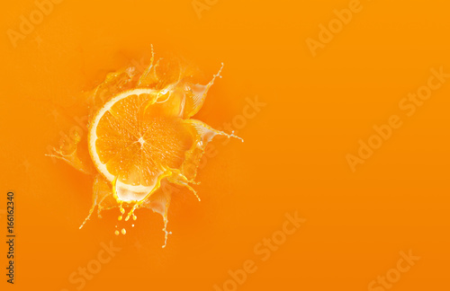 Canvas Prints Juice Slide cut piece of orange drop on orange background with orange juice splash water with copy space